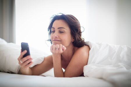 Beautiful young woman using her smart phone in bed, following social media, being quite addicted to this device without realizing
