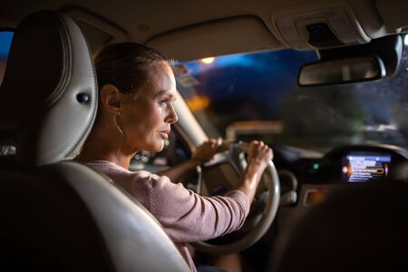 Young female driver driving her car at night (color toned image; shallow DOF) Stock Photo