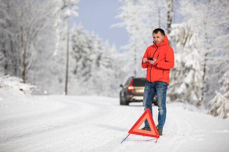 Bel homme mettant en place un triangle d'avertissement et appelant à l'aide après que sa voiture est tombée en panne au milieu de nulle part par une journée d'hiver glaciale