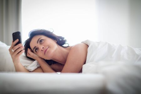 Beautiful young woman using her smart phone in bed, following social media, being quite addicted to this device without realizing Banco de Imagens - 126191631
