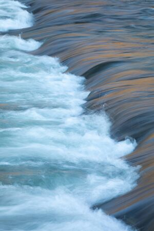 Water concept - river water flowing with light reflecting of its surface - long exposure shot