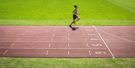 Runner on a running track finishing a race first (motion blurred image) Фото со стока