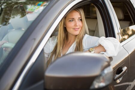 Pretty, young woman  driving a car -Invitation to travel. Car rental or vacation. Stock fotó