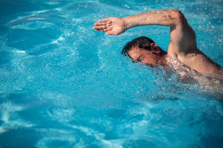 Male swimmer swimming crawl in an outdoor pool - keeping fit