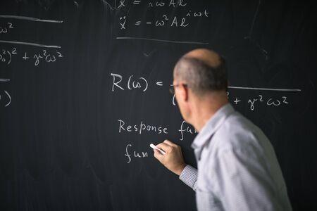 Math teacher drawing   fuction graph on a blackboard during mathclass (shallow DOF, color toned image) Stok Fotoğraf