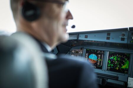 Pilot in  a commercial airliner airplane flight cockpit during takeoff