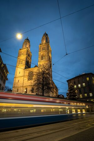 Zurich, Switzerland - view of the Grossmünster church with motion blurred tramway during Chrostmas time Stock Photo