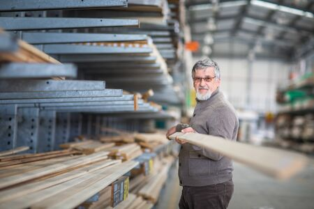 Man choosing and buying construction wood in a DIY store for his DIY home re-modeling project Stock Photo - 128059519