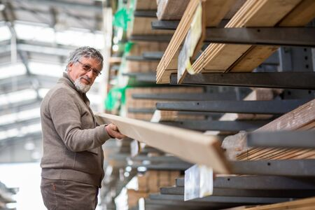 Man choosing and buying construction wood in a DIY store for his DIY home re-modeling project Stock Photo - 128059526