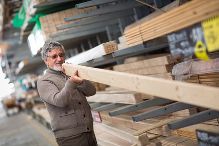 Man choosing and buying construction wood in a DIY store for his DIY home re-modeling project Stock Photo - 128059668