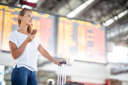 Young woman with her luggage at an international airport, before going through the check-in and the security check before her flight Stock Photo - 128572520