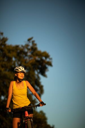 Pretty, young woman biking on a mountain bike enjoying healthy active lifestyle outdoors in summer (shallow DOF)