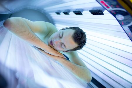 Handsome young man relaxing during a tanning session in a modern solarium, taking care of himself, enjoying the artificial sunlight. Stockfoto - 128572900