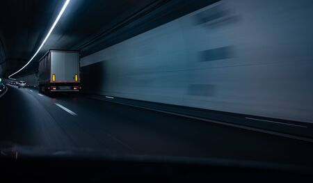 Cars on a highway going through a long modern tunnel (motion blurred image; color toned image) Banco de Imagens