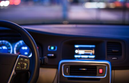 Interior of a modern car at night in a city (shallow DOF; color toned image)