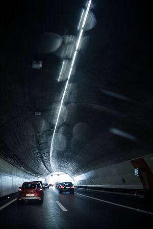 Cars on a highway going through a long modern tunnel (motion blurred image; color toned image) Stock Photo
