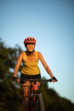 Pretty, young woman biking on a mountain bike enjoying healthy active lifestyle outdoors in summer (shallow DOF) Stock Photo