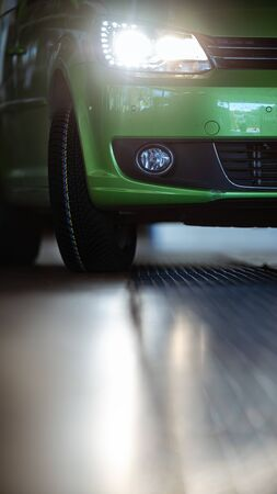 Car in a garage for maintenance, oiltyre change (shallow DOF; color toned image)