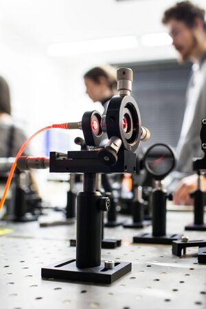 Quantum optics lab installations with laser, irises, appertures - laser reflect on optic table un quantum laboratory