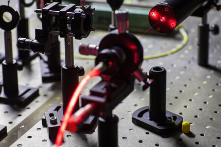 Quantum optics lab installations with laser, irises, appertures - laser reflect on optic table un quantum laboratory