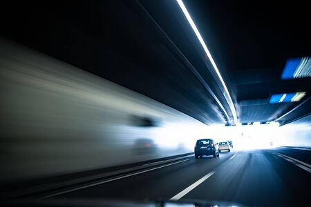 Cars on a highway going through a long modern tunnel (motion blurred image; color toned image) Фото со стока