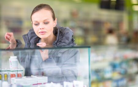 Young woman looking for the right pillsher prescription in a modern pharmacy (shallow DOF; color toned image) Banco de Imagens