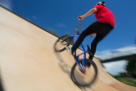 Bmx rider jumping over on a U ramp in a skatepark (motion blurred image)
