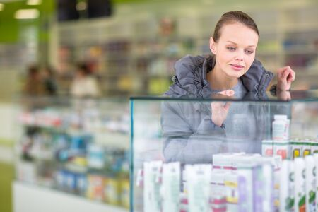 Young woman looking for the right pillsher prescription in a modern pharmacy (shallow DOF; color toned image) Stock Photo