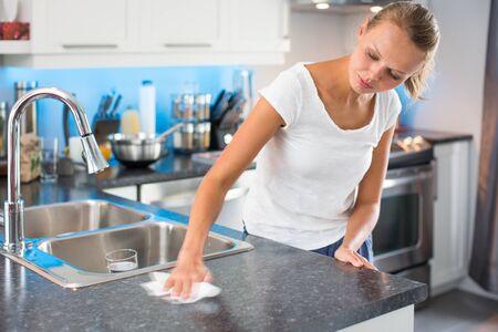 Mujer joven y bonita en su cocina moderna, limpia y luminosa, limpiando la cocina (imágenes en tonos de color; DOF superficial)