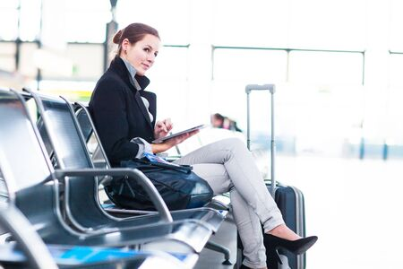 Young female passenger at the airport, using her tablet computer while waiting for her flight (color toned image)