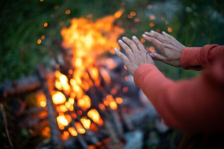 Young woman making fire while camping outdoors, in an alpine wilderness - warming up her hands near the fire