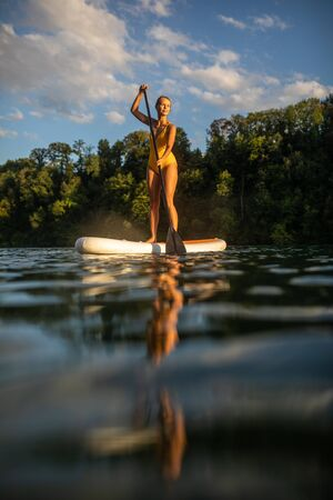 SUP Stand up paddle board concept - Pretty, young woman paddle boarding on a lovely lake in warm late afternoon light - shot from underwater