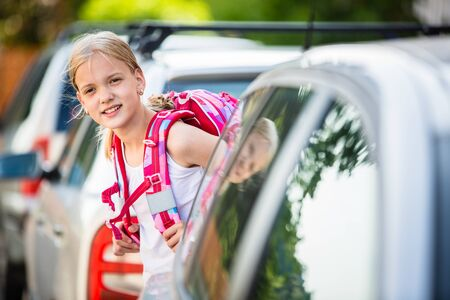 Cute little girl going home from school, looking well before crossing the street Reklamní fotografie