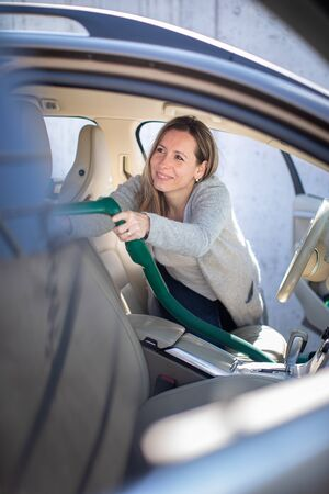Pretty, middle aged woman vacuum cleaning the interior of a luxury car