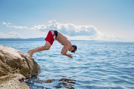 Young man having fun and taking a dive in the sea Zdjęcie Seryjne - 129902609