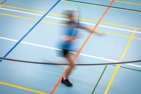 Badminton player in fast motion on a badminton court in a gymnasium (motion blur technique used)