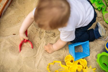 Little kid playing in sand with many plastic toys Stock Photo
