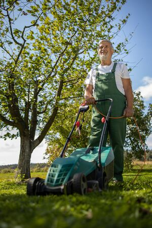 Senior gardenr gardening in his permaculture garden - mowing the lawn with an electrical lawn mower