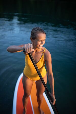 SUP Stand up paddle board concept - Pretty, young woman paddle boarding on a lovely lake in warm late afternoon light - shot from underwater Banco de Imagens - 130277650