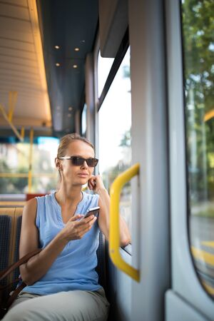 Young woman on a city tram, heading for the office early, before the rush hour begins Banque d'images - 130277636