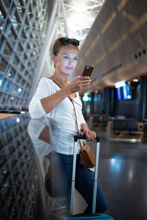 Young woman with her luggage at an international airport, waiting for her flight in the lounge zone after going through the  security check procedure