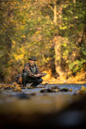 Handsome fly fisherman working the line and the fishing rod while fly fishing on a splendid mountain river for rainbow trout Stock fotó