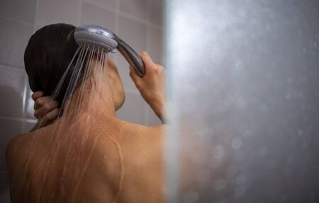 Pretty, young woman taking a long hot shower washing her hair in a modern design bathroom