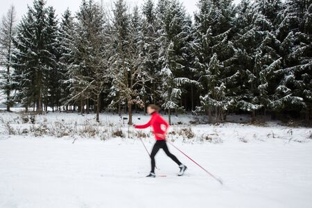 Cross-country skiing: young woman cross-country skiing on a  winter day (motion blurred image) 写真素材