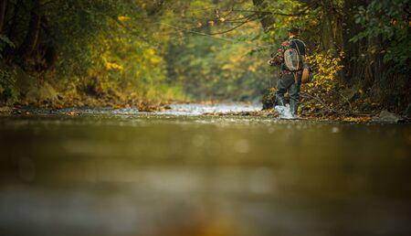 Fliegenfischer, der an Schnur und Angelrute arbeitet, während er auf einem herrlichen Bergfluss auf Regenbogenforellen fliegt