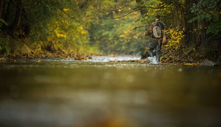 Fly fisherman working on line and fishing rod while fly fishing on splendid mountain river for rainbow trout