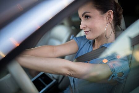 Pretty, young woman  driving a car. Car rental or vacation.