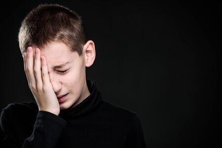 Niño afligido por el dolor - sentimiento intenso dolor, remordimiento, tristeza - retrato de estudio - serie de emociones vívidas