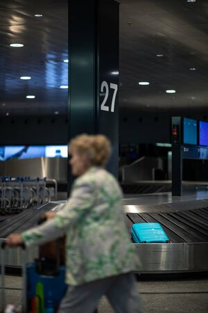 Unclaimed luggage concept - suitcase going around on the conveyor belt at an international airport, at the baggage claim zone - motion blurred image