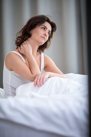 Pretty, young woman with stiff neck, suffering from back pain, in her bed in the morning